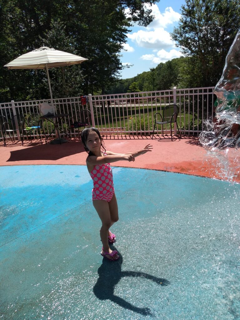 image of child play at splash pad at the dinosaur place in Montville, ct.