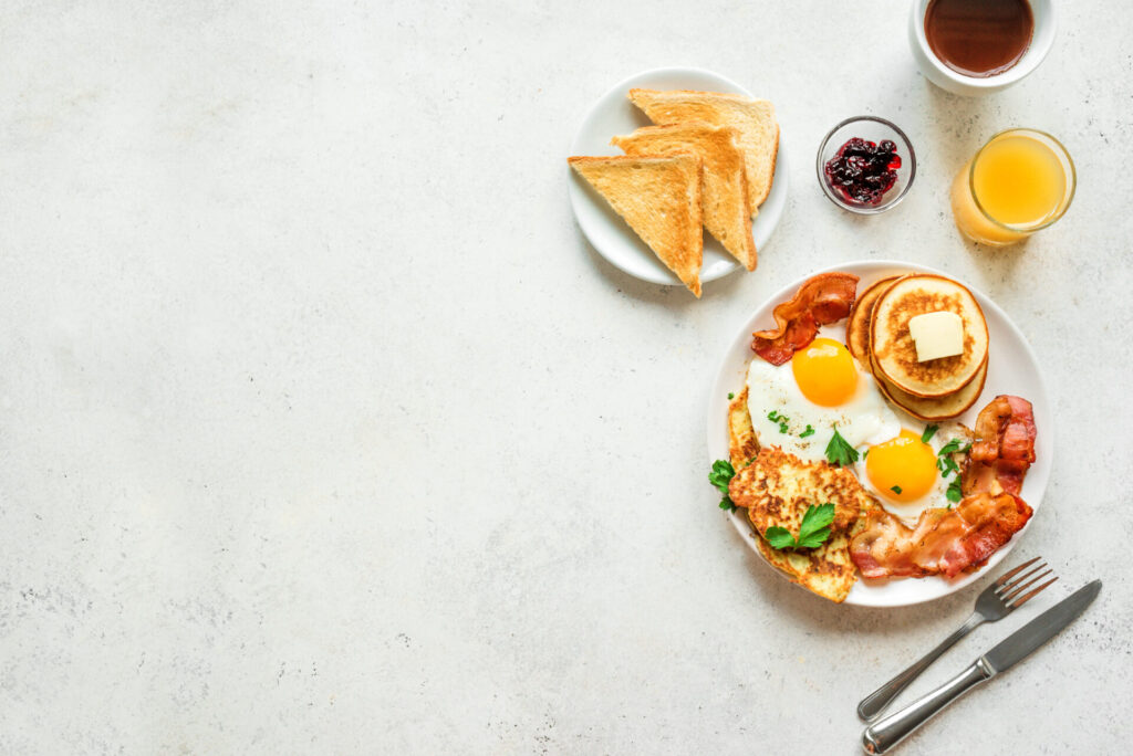image of breakfast plate with bacon, toast, and eggs.