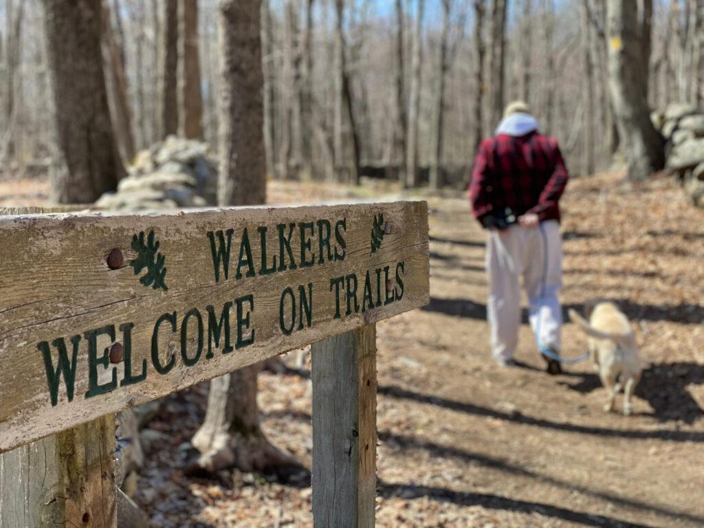 image of man walking dog on walking trails in ct.