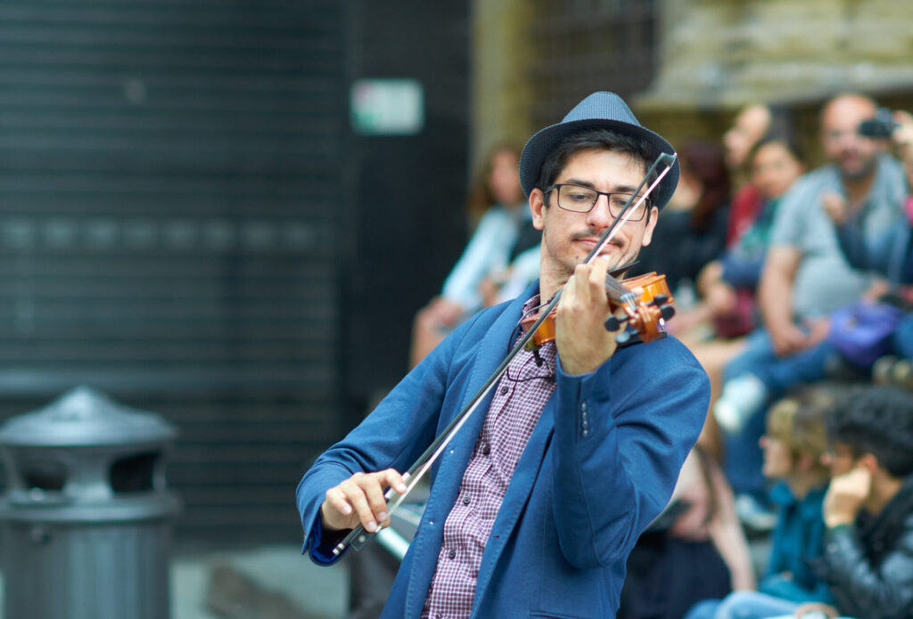 image of man playing violin in artsy town in Connecticut.